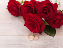 Wedding rings and wedding bouquet of red roses. On wooden table. horizontally Royalty Free Stock Photos