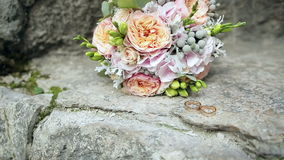 Wedding rings and wedding bouquet. Wedding rings and wedding bouquet on stone stock video