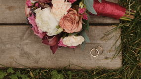 Wedding rings and wedding bouquet at wooden and grass surface. Wedding rings and wedding bouquet at wooden and grass lawn surface stock footage