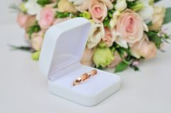 Wedding rings and flowers. Wedding rings wedding rings on a bouquet of white flowers Royalty Free Stock Images