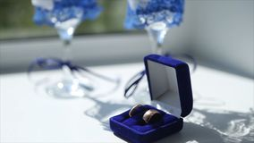 Wedding rings and wedding wine glasses on the table in the morning of the wedding day. stock image