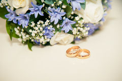 Wedding rings on a white background with a bouquet of blue ribbo Royalty Free Stock Photography