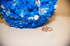 Wedding rings on a white background with a bouquet of blue ribbo Royalty Free Stock Photos