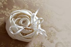 Wedding rings on white beautiful cushion in the form of a rose. With space for text on the right stock image