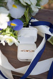 Wedding rings and white blue flower bouquet Royalty Free Stock Photos