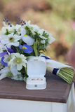 Wedding rings and white blue flower bouquet Royalty Free Stock Image