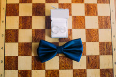 Wedding rings in white box along with bow-tie lie on chessboard. Close up shot of groom's accessories Royalty Free Stock Photos