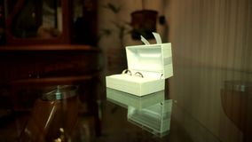Wedding Rings In White Box. The man puts on the table, two wedding rings in white box stock footage