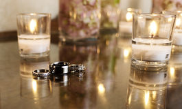 Jewelry:Wedding Rings with White Candles. The bride and grooms wedding rings showcased with a white candle and table decoration at the wedding reception Royalty Free Stock Photos