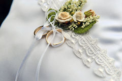 Wedding rings on a white cushion, rose decoration. Royalty Free Stock Image