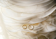 Wedding rings on white dress detail. Wedding rings golden on white dress detail royalty free stock image