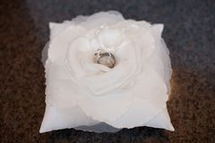 Wedding rings on a white flower and pillow stock photography