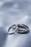 Wedding rings - white gold. Marriage - wedding rings on silver silk background Stock Image