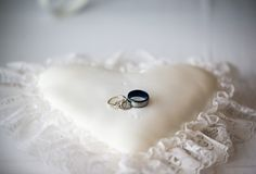 Wedding rings on a white heart shaped pillow stock photos