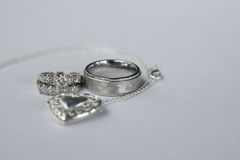 Wedding rings on white with a locket. At reception Stock Photo