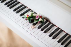 Wedding rings on white piano with flowers royalty free stock photo