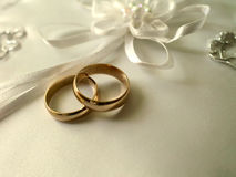 Wedding rings on a white pillow stock images