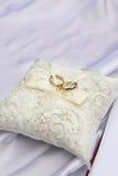 Wedding rings on a white pillow . Stock Photos