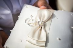 Wedding rings on white pillow holded Stock Photos