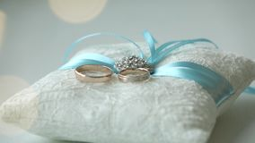 Wedding rings on a white pillow.