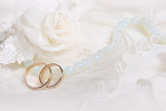 Wedding rings and white rose. On lace light background stock images