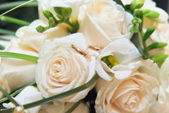 Wedding rings on a white roses Stock Photos