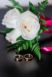 Wedding rings and white roses stock photography