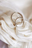 Wedding rings on white satin fabric Royalty Free Stock Photo