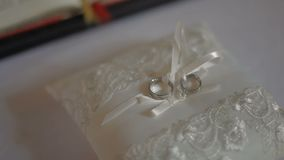Wedding rings on a white silk pillow stock video footage
