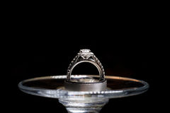 Wedding rings on a wine glass. Isolated on black Stock Images