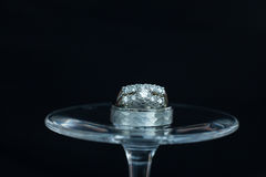 Wedding rings on a wine glass. At reception Stock Images