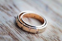Wedding rings on wood panel.  Royalty Free Stock Photo