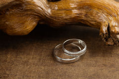 Wedding rings on wood. Two platinum wedding rings on wood background. Bride ring with diamonds. Shallow focus. Rustic concept Stock Images