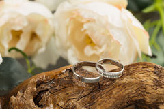 Wedding rings on wood. Two platinum wedding rings on wood background with flowers. Bride ring with diamonds. Shallow focus. Rustic wed concept Stock Photo