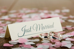Wedding rings on a wooden background with confetti Royalty Free Stock Photos