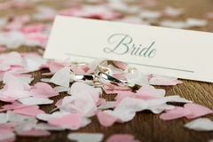 Wedding rings on a wooden background with confetti Stock Image
