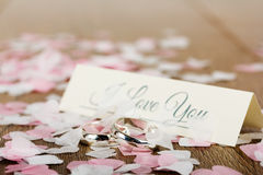 Wedding rings on a wooden background with confetti Stock Photo