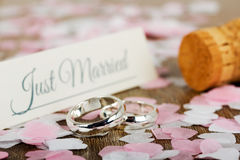 Wedding rings on a wooden background with confetti Royalty Free Stock Photo