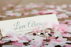 Wedding rings on a wooden background with confetti Royalty Free Stock Photography