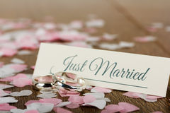 Wedding rings on a wooden background with confetti Royalty Free Stock Image