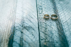 Wedding rings on a wooden background Stock Photos