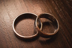 Wedding rings on wooden background Stock Photos