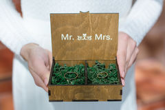Wedding rings in a wooden box filled with moss on the green grass Royalty Free Stock Images