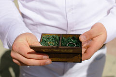 Wedding rings in a wooden box filled with moss on the green grass Royalty Free Stock Photography