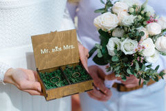 Wedding rings in a wooden box filled with moss on the green grass Stock Photography
