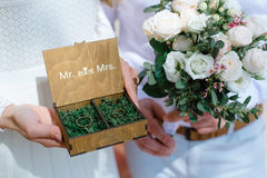 Wedding rings in a wooden box filled with moss on the green grass Stock Images