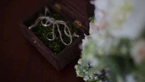 Wedding rings in a wooden box filled with moss on the table. Wooden box with wedding rings lies near the bridal bouquet. Of the bride from natural flowers stock video footage