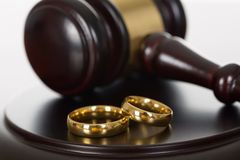 Wedding rings and wooden gavel. Close-up Of Wedding Rings And Wooden Gavel Stock Photography