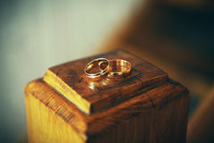Wedding rings on a wooden stand. Wedding rings are on the vintage wooden surface Royalty Free Stock Photo
