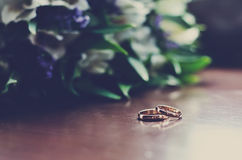 Wedding rings on wooden surface. Beautiful wedding rings lie on a wooden surface against the background of a bouquet of flowers Royalty Free Stock Photos